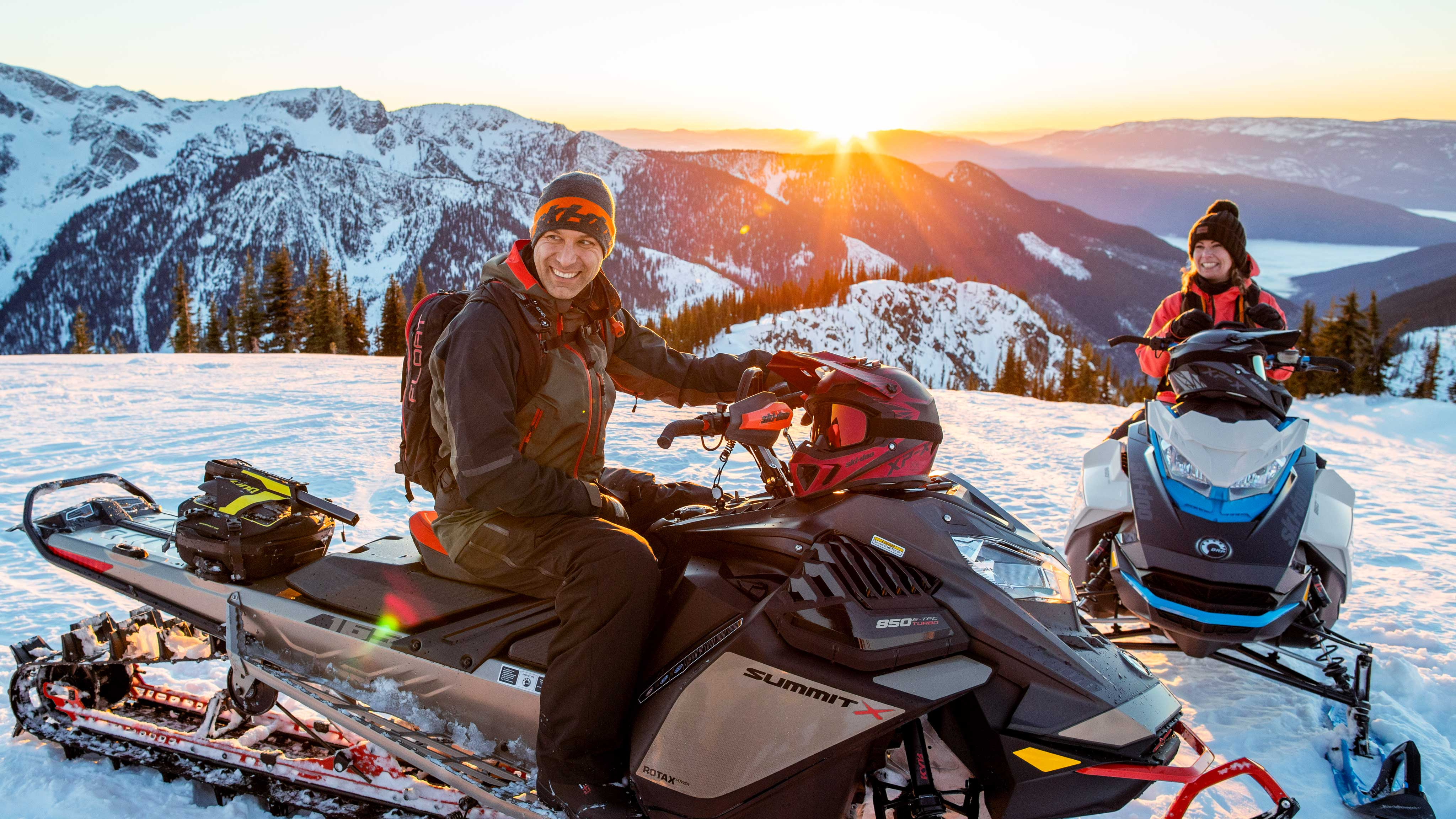 Couple enjoying a Snowmobile backcountry ride at sunset