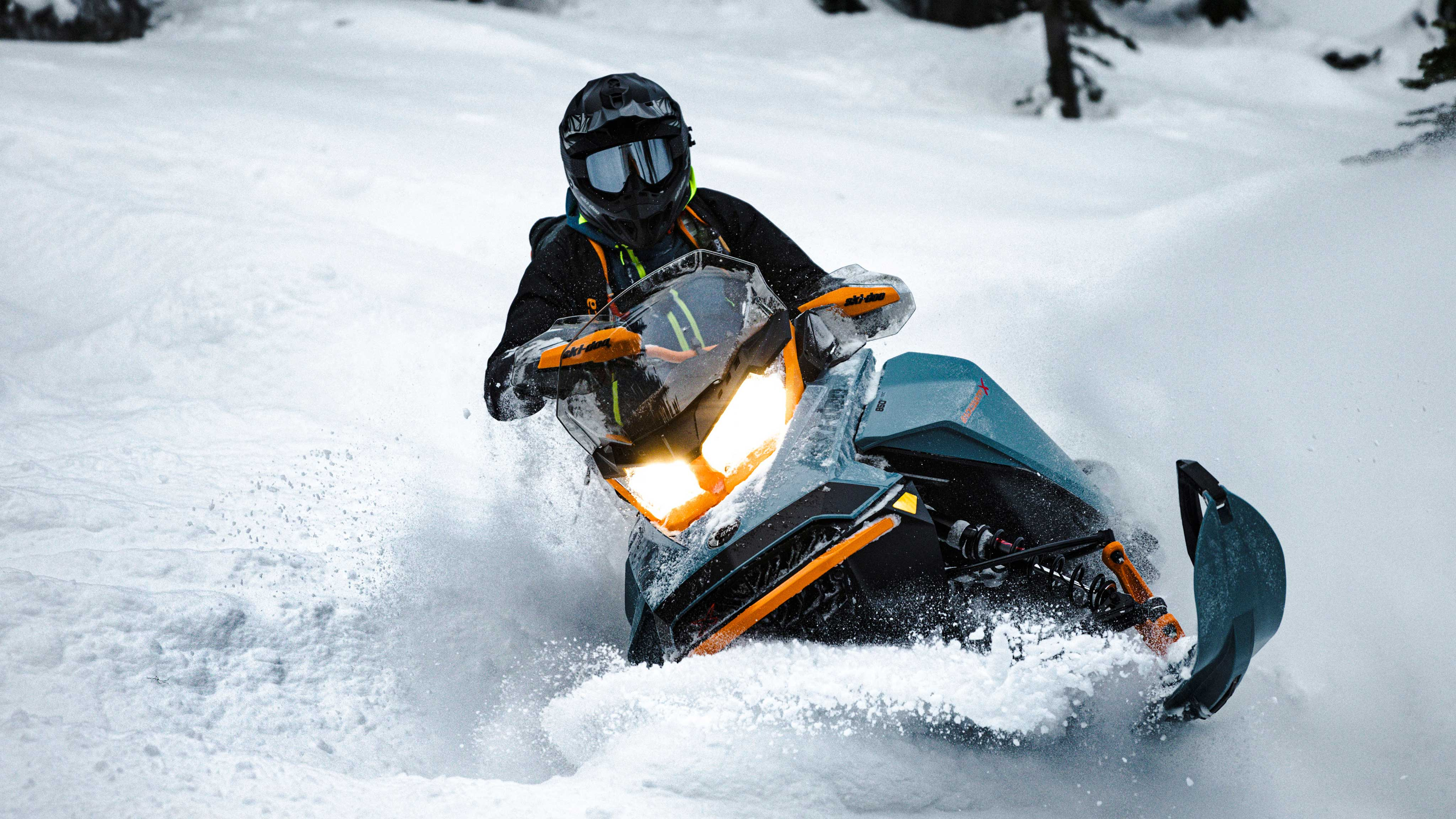Rider riding a blue Ski-Doo Backcountry snowmobile in deep snow