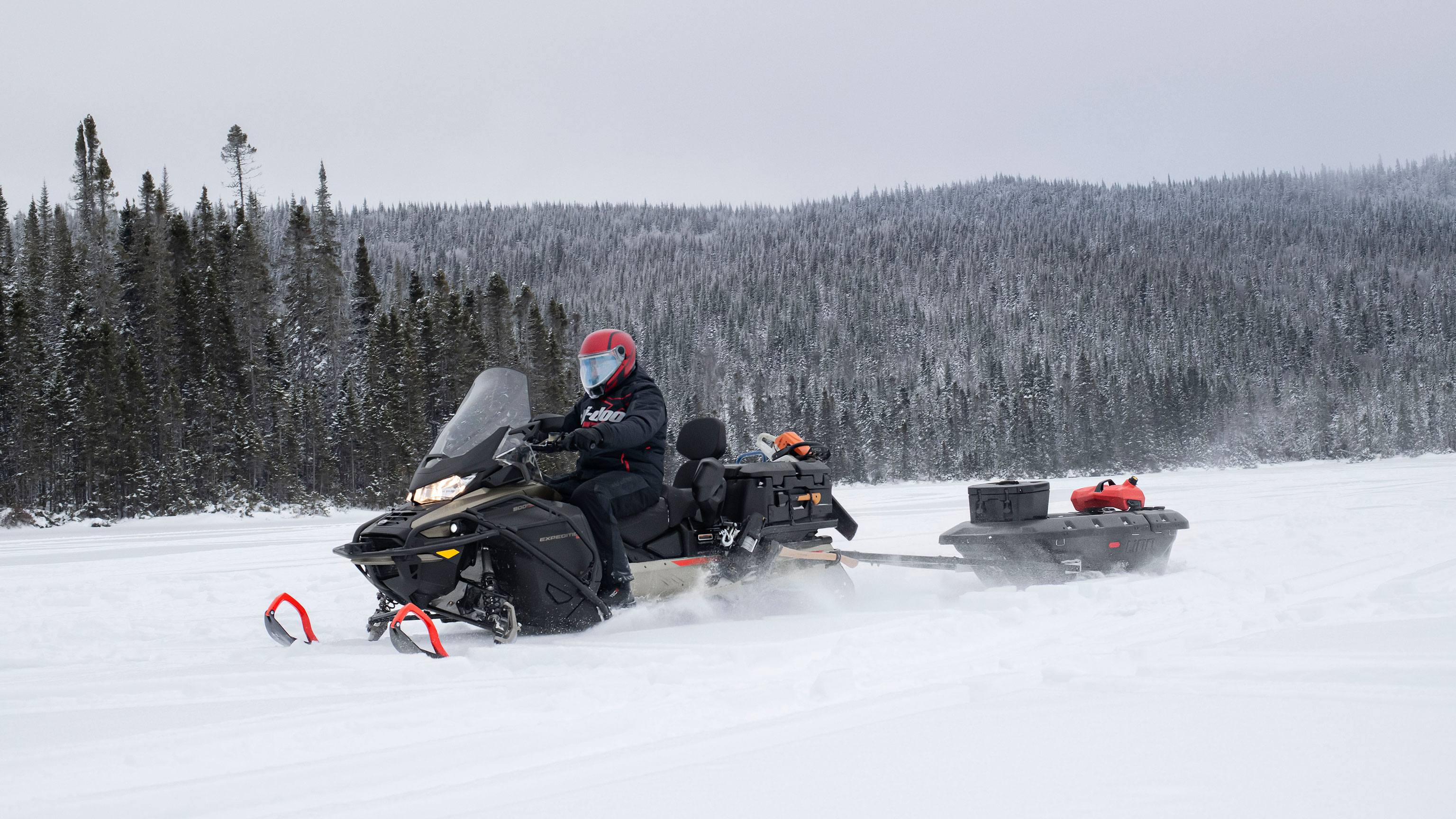 Man towing a sleigh with his 2022 Ski-Doo Expedition