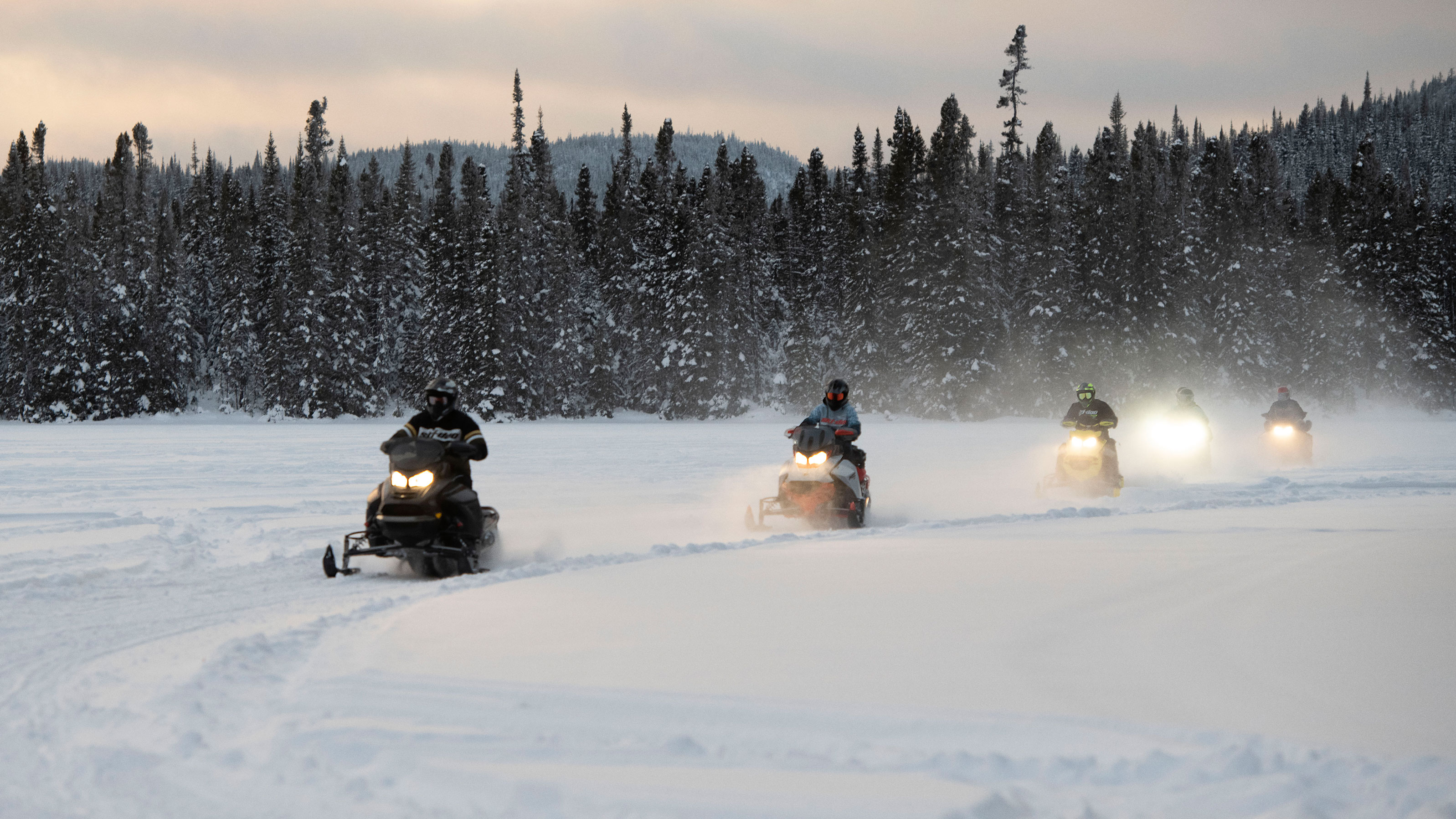 Group of riders snowmobiling at the sunset