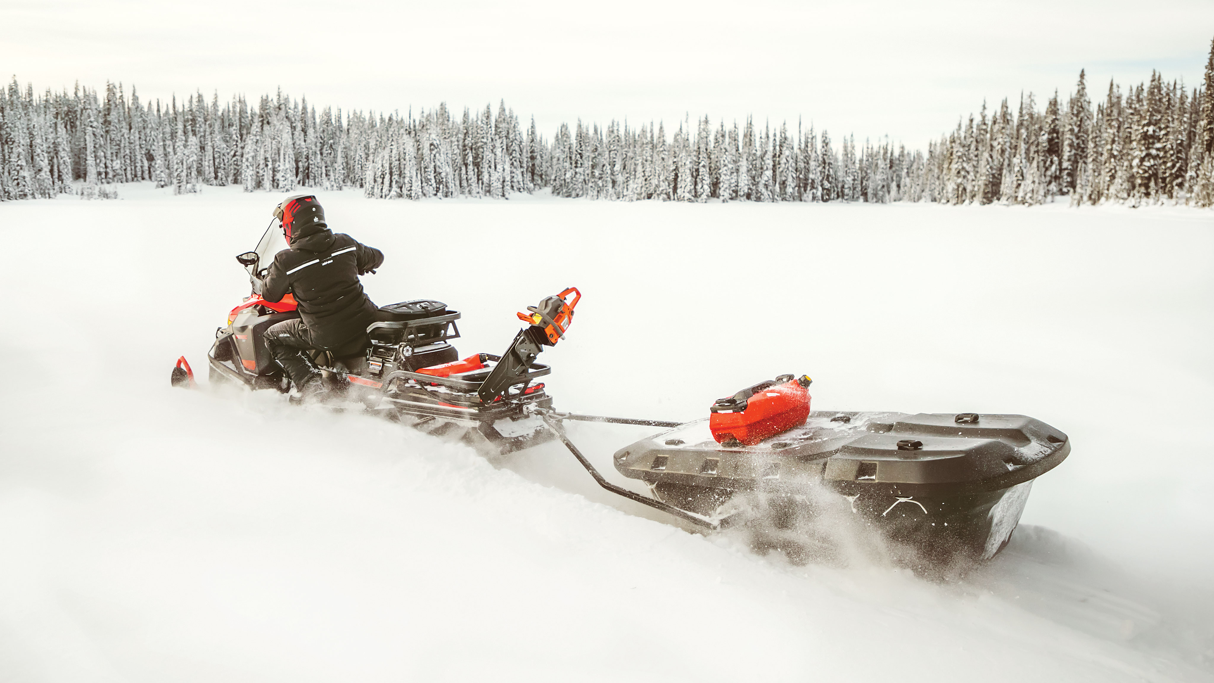 Man riding a Ski-Doo Skandic with a Sleigh in Deep-Snow